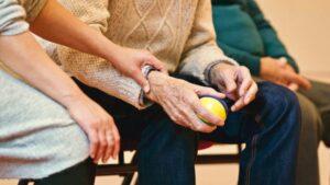 Older male holding foam ball for hand exercises