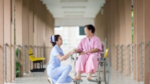 Asian woman in wheelchair smiling, nurse standing by her side in hospital