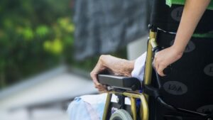Arm of elderly woman resting on arm rest of wheelchair