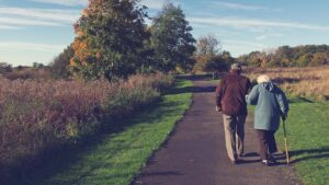 Elderly man and woman walking hand in hand on an empty road in the countryside
