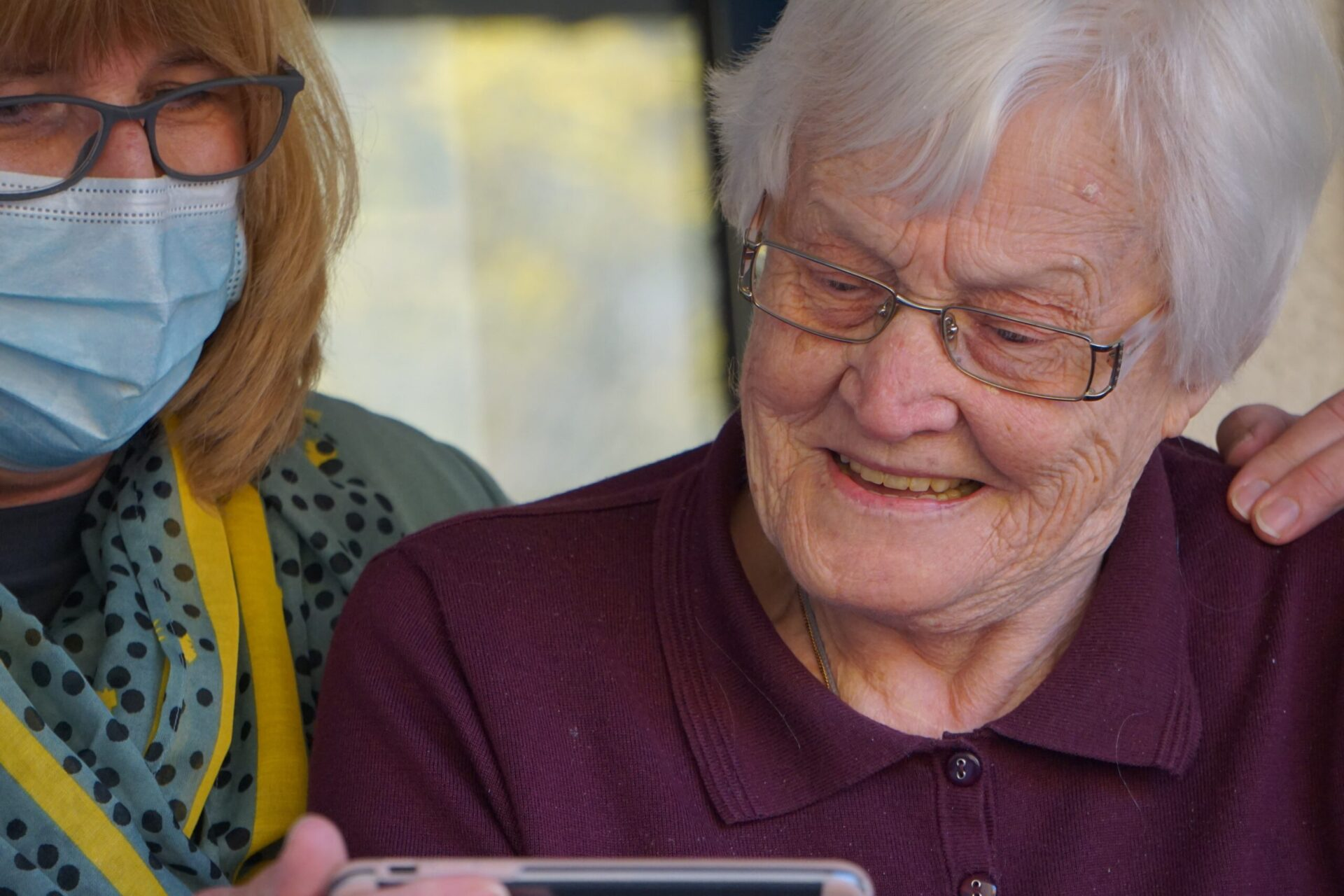 Caregiver wearing mask and elderly woman looking at a phone