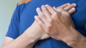 Man wearing blue shirt putting both hands on his chest.