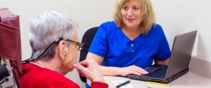 Lady in speech therapy with stroke survivor elderly woman