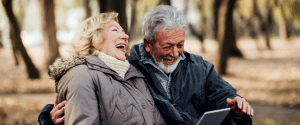 Older man and woman sitting on a park bench laughing